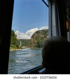 Silhouette of a passenger on a KD cruise line river boat as they peer out the window at the famous Lorelei Rock, the most dangerous section of the Rhine,  Kaub Germany. Aug 2019