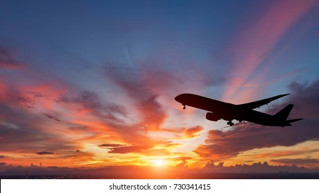 Silhouette of a passenger plane flying in sunset.