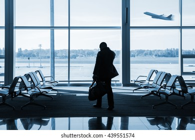 silhouette of passenger waiting for the flight inside airport terminal lounge, blue toned