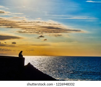 Silhouette of a pensive woman sitting on a wall facing a twilight background.