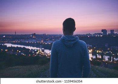 Silhouette of the pensive young man waiting for sunrise on the hill against urban skyline. Prague, Czech Republic.