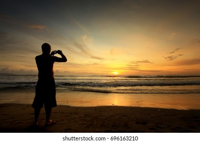 Silhouette of People Capturing Sunset