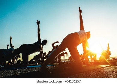 Silhouette of people doing yoga outdoor - Meditation and sport concept for healthy and relaxing lifestyle - Focus on close up woman