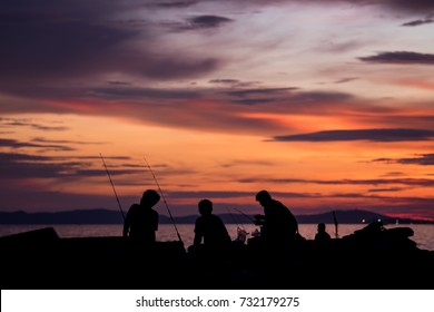 Silhouette of people fishing at the beach in the evening with twilight background, waiting for fish to hunt.