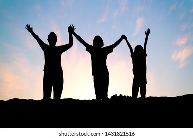 silhouette of people group with raised hands on the mountain at the sunset or sunrise time.