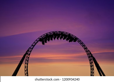 Silhouette of people having fun on a roller-coaster in an amusement park at sunset. Adrenalin concept.
