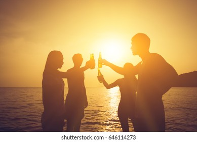 Silhouette of people having party, clanging beer bottles, making a toast at the beach in sunset