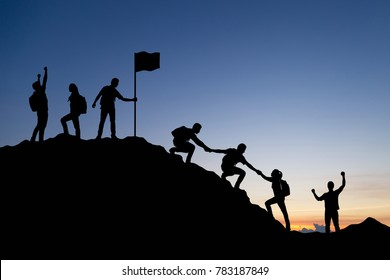 Silhouette of people helping each other hike up a mountain and celebrating at sunset background. Business, teamwork, success, help and goal concept.