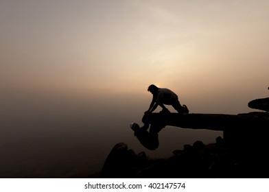silhouette people helping hand of friend on top mountainat Phu Bakdai, Phu Ruea District, Loei Province, Thailand.