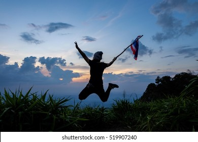 Silhouette of people hold Thai flag on hand and jumping on Khao Chor peak mountain, Khaoyai Nataion park, Thailand