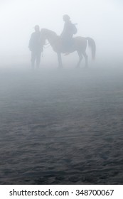 Silhouette of people and horses in fog and mist of sulfur volcano Bromo