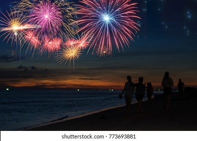 Silhouette people looking beautiful fireworks display on the beach ,celebration new year night concept