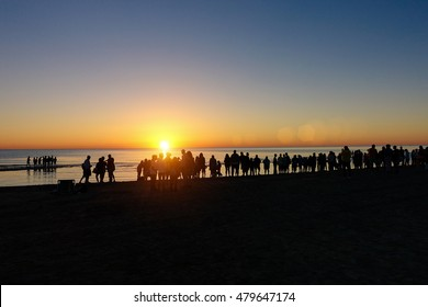 Silhouette of people looking sunrise on beach in summer time - Vacation and summer concept - Soft saturated filter