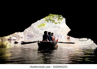 the silhouette of the people on the boat at the entrance of the cave