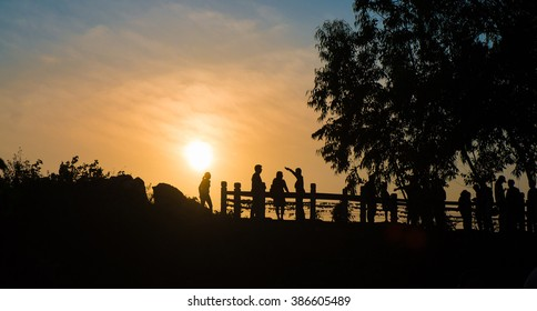 silhouette of people on hill and sunset