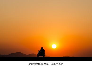Silhouette people on motorcycle at sunset time with mountain and beautiful orange background