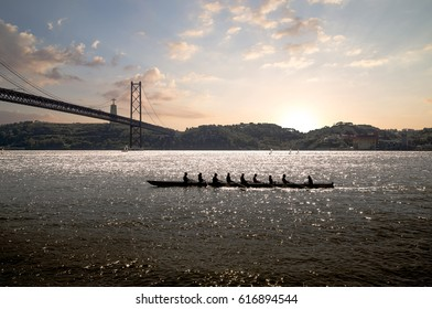 silhouette of people on rowing boat on the sea with suspension bridge in the background during sunset. Lisbon, Portugal.