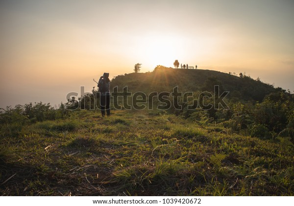 silhouette of people on the top of mountain with sun set background and sun light flare