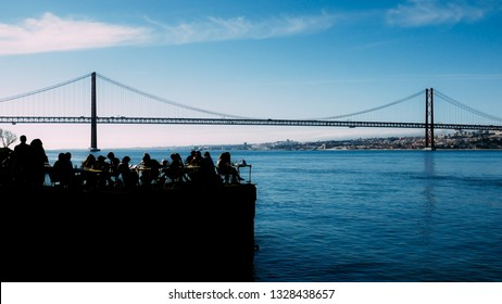 Silhouette of people relaxing in outdoor restaurant terrace overlooking the iconic 25 April bridge in Lisbon, Portugal,