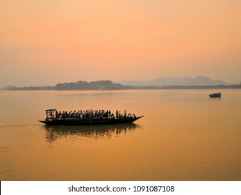 Silhouette of people sailing in a boat over river Brahmaputra during sunset.