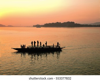 Silhouette of people sailing in a boat over river Brahmaputra during sunset