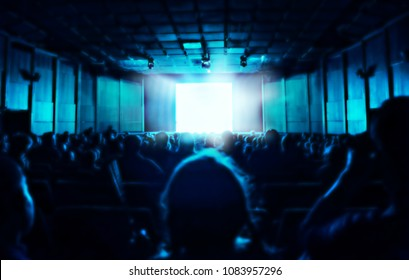 silhouette of people sitting in dark cinema hall, blue glow from screen, blurred background