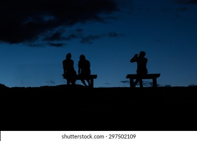 Silhouette people sitting on the branch after sunset