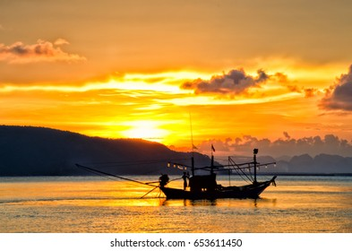 Silhouette of people in a small fishing boat moving in the background on the Sea of Chumphon Province, Thailand.