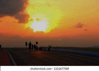 silhouette people standing on high ay with sunset sky background