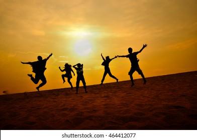 Silhouette-Leute mit Sonnenuntergang auf Sand, unscharfer und niedriger Schlüssel