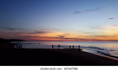 Silhouette of people taking picture of landscape during sunrise Scenic View Of Beach Against Sky During Sunset.