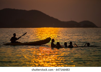 Silhouette of people taking their lifestyle moment reflection gold of water during sunset timing with beautiful mountain background. Concept of people and family lifestyle