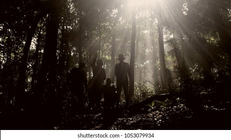 silhouette people travel adventure in the jungle with ray light in the morning