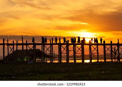 silhouette of people traveling across the U Bein Bridge in the evening. U bein bridge, Taungthaman lake, Amarapura, Burma.