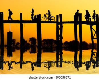 silhouette of people traveling across the U Bein Bridge in the evening. U bein bridge, Taungthaman lake, Amarapura, Burma. It is the oldest and longest teak wooden bridge in the world