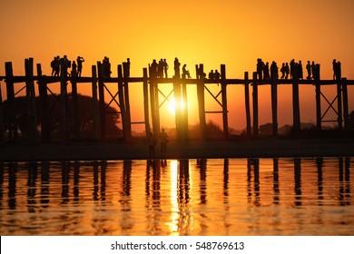 Silhouette of people traveling across the U Bein Bridge in the evening. Mandalay Myanmar