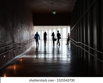 Silhouette of people walking up a dark ramp illuminated by outdoor light coming from glass walls in the distance