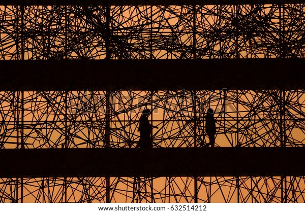 silhouette people walking in an intricate modern architecture during sunset sky.
