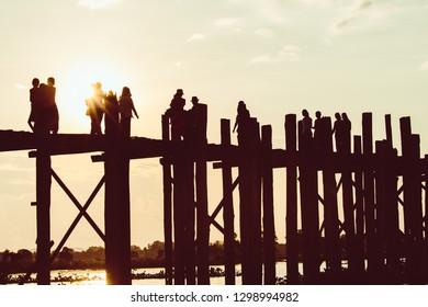 Silhouette of people walking on Bridge U-Bein at sunset scene in Amarapura, Mandalay, Myanmar