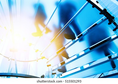 Silhouette people walking on glass staircase