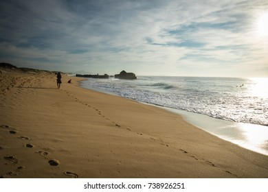silhouette of people walking in scenic beautiful seascape with waves on hot sunny day in october on atlantic coast, capbreton, france