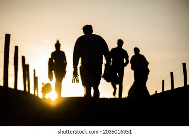 silhouette of people walking through the dunes to the beach during sunrise