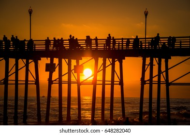 Silhouette of people watching the sunset on the Oceanside Pier in California