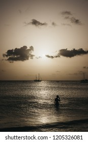 Silhouette of a person in calm waters of Carlisle Bay in Bridgetown, Barbados, in the evening, silhouettes of boats on the horizon.