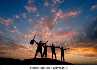 Silhouette person friends young male musician guitarist on top of a rock mountain hill hands spread with blue sunset sky and fluffy orange clouds, friendship freedom concept, copy space for text paste