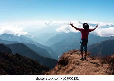 Silhouette of Person in hiking Clothing and Hat with Arms raised and spread making embrace the world gesture staying on grassy Peak and overlooking Mountain Scenery