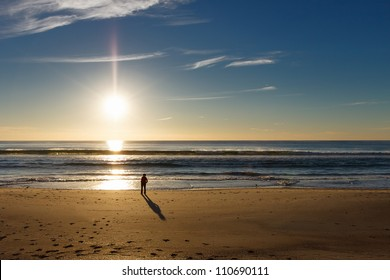 silhouette of person on beach watching sunrise over the sea