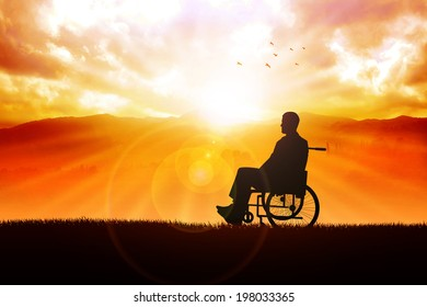 Silhouette of a person on wheelchair in the outdoor with sunrise and mountain view as the background