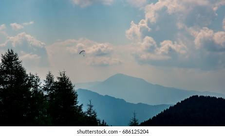 Silhouette of a person parapenting or paragliding over the blue misty Italian mountains with the dark trees of the forest on the foreground