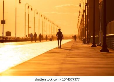 Silhouette of a person running on a boardwalk at sunset. Outdoor activity under golden light - Long Beach New York